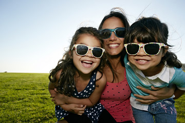 Mother and daughters smiling in field