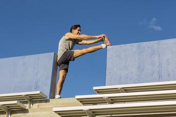Hispanic athlete stretching on bleachers
