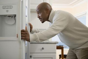 African man looking in refrigerator
