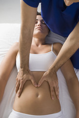 Chiropractor adjusting woman's spine