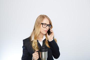 blonde geschäftsfrau mit  kaffeebecher und mobil telefon