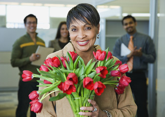 African businesswoman holding bouquet of flowers