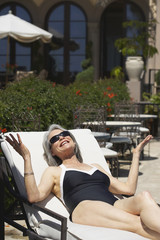 Woman at poolside laying on lounge chair