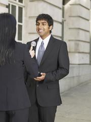 Indian businessman being interviewed on sidewalk