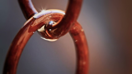 Water drops falling on a metal chain