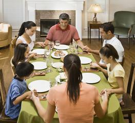 Hispanic family praying at dinner table