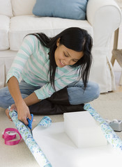 Pacific Islander woman wrapping gift