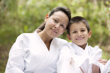 Hispanic mother and son wearing martial arts robes