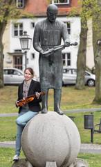 Statue und Geigerin