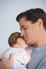 Hispanic father hugging baby