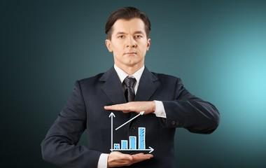 Success. Image of businessman holding alarmclock against
