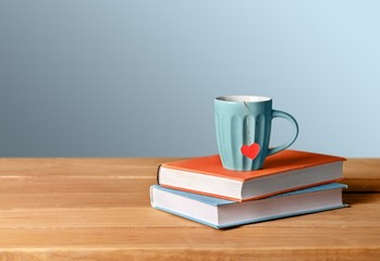 You. Blue cup with red heart on green and orange books on grunge
