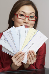 Asian businesswoman holding checks