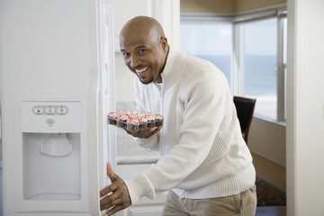 African man holding cupcakes next to refrigerator