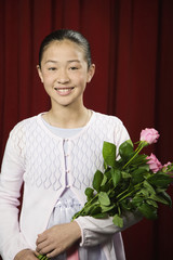 Asian girl holding flowers on stage