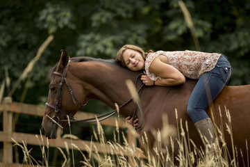 Caucasian woman laying on horse in pen