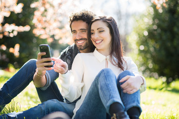 Couple looking to a smartphone in a park