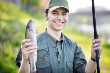 Smiling fisherman holding a fish