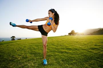Hispanic woman lifting weights in field