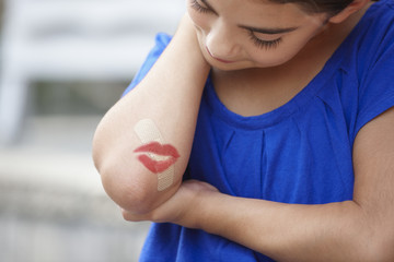 Caucasian girl with lipstick kiss over bandage on elbow