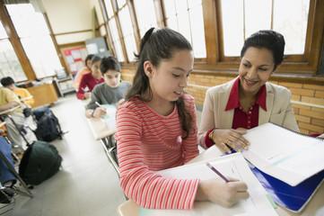 Hispanic school teacher helping student