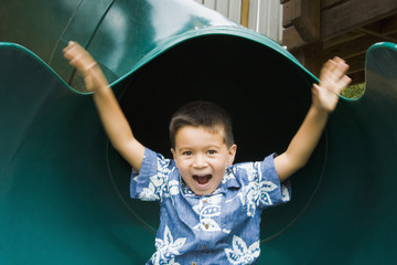 Mixed race boy sliding in playground