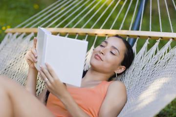 Hispanic woman laying in hammock reading