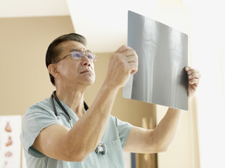 Senior Asian male doctor looking at x-ray