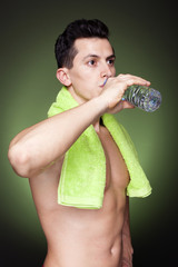 Young athletic man drinking a bottle of water against dark backg