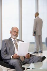 Senior African businessman holding paperwork