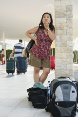 Asian woman with luggage waiting in airport