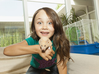 Girl playing with pet hamster