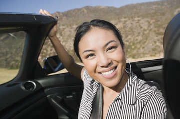 Asian woman sitting in convertible car