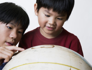 Asian brothers looking at globe