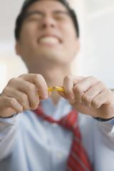 Korean businessman breaking pencil