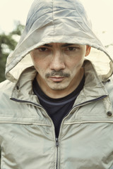 Asian man wearing hood outdoors