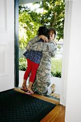 Mixed race soldier mother hugging daughter in front door