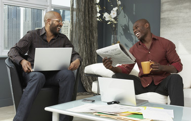 African businessmen with laptops in lobby