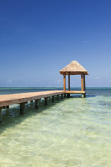 Pier over turquoise blue water on the beach at Cancun