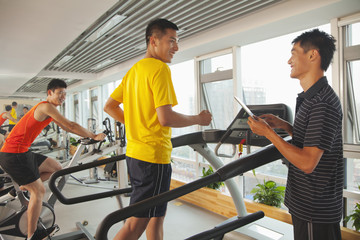 Chinese man talking to trainer with digital tablet in gym