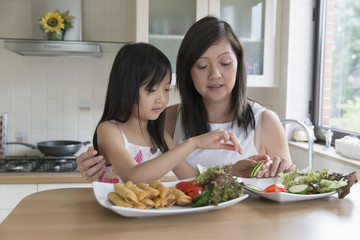 Asian mother and daughter eating in kitchen