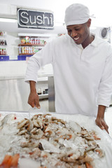 Mixed race grocer preparing seafood in market