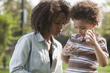 Mother and son examining insect in park