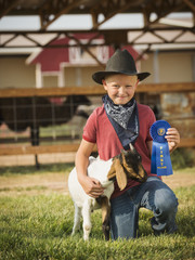 Caucasian boy with prize winning goat on farm