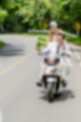 Blurry background, Just married. Groom and bride on the motorcyc