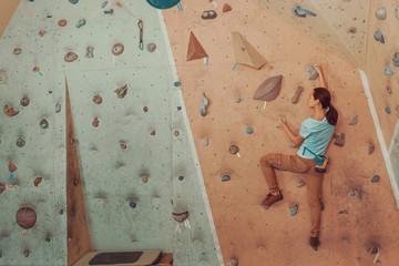 Young woman climbing artificial boulder in gym