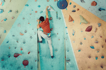 Free climber man climbing artificial boulder