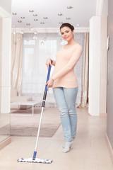 Woman mopping floor in living room