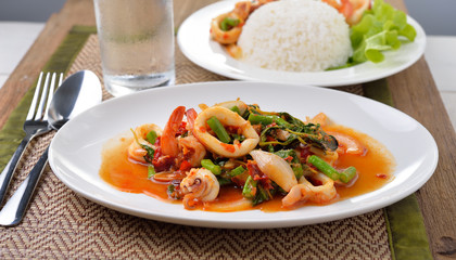 stir fried squid with chilli and basil on white plate