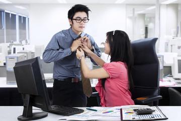 Businesswoman helping her partner for dressing